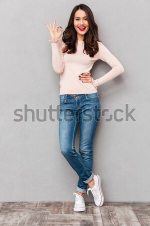 Full-length photo of energetic woman wearing sneakers and jeans  Stock photo © deandrobot