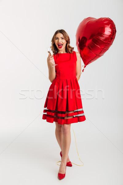 Full length portrait of a joyful young woman Stock photo © deandrobot