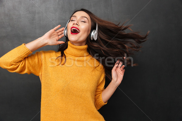 Playful brunette woman in sweater and headphone listening music Stock photo © deandrobot