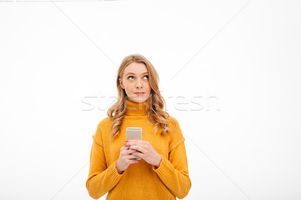 Thinking young woman using mobile phone. Stock photo © deandrobot