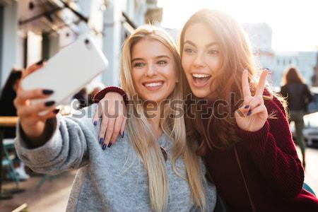 Stock photo: Two smiling young girls watching video on mobile phone