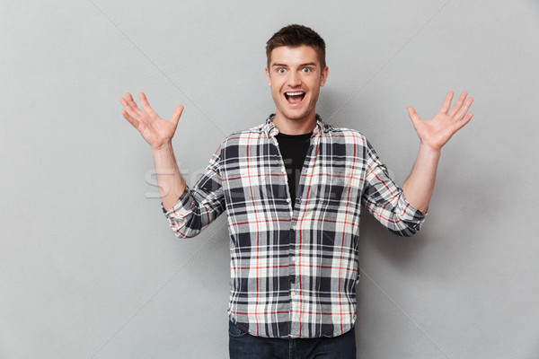 Portrait of an excited young man with hands raised Stock photo © deandrobot
