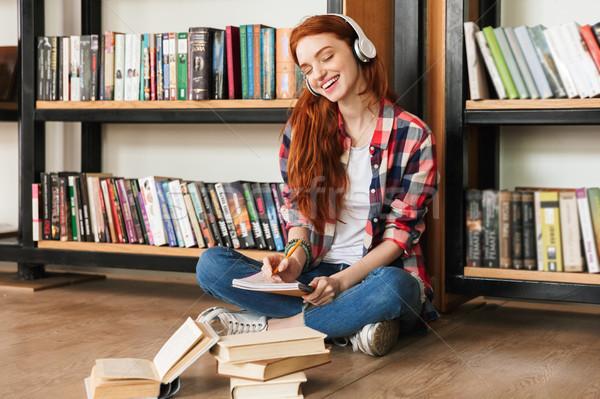 Glimlachend tienermeisje huiswerk vergadering bibliotheek luisteren naar muziek Stockfoto © deandrobot