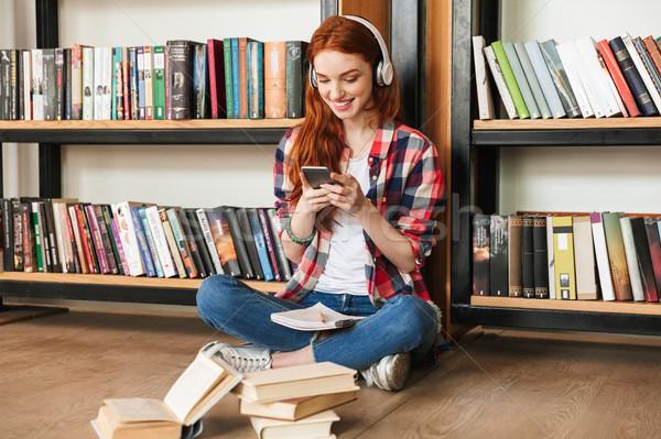 Lächelnd Hausaufgaben Sitzung Bibliothek Musik hören Stock foto © deandrobot