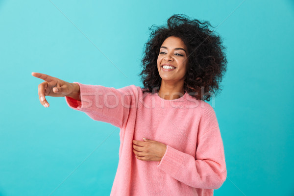 Image of american curly woman in pink shirt looking aside and po Stock photo © deandrobot