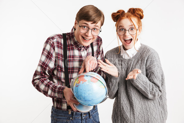 Happy couple of school nerds holding earth globe Stock photo © deandrobot