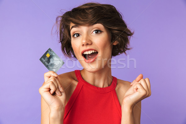 Surprised happy Pretty brunette woman holding credit card and rejoices Stock photo © deandrobot