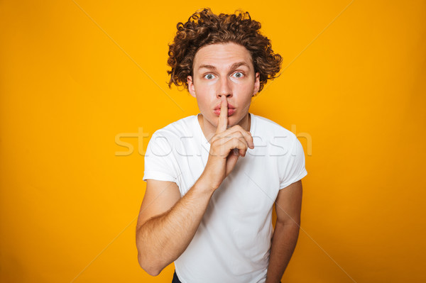 Portrait of a shocked curly haired man showing silence Stock photo © deandrobot
