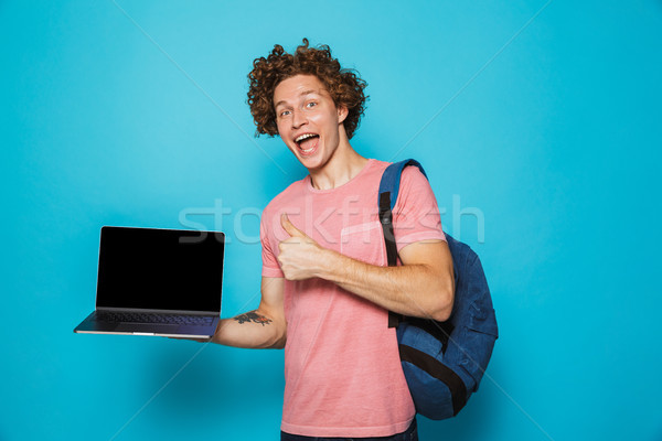 Photo of university guy with curly hair wearing casual clothing  Stock photo © deandrobot
