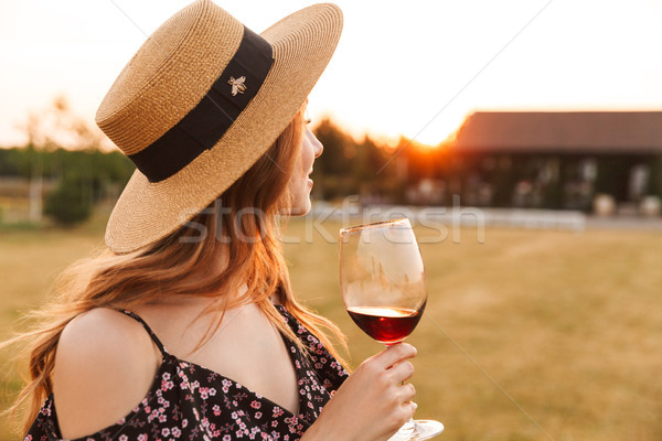 Stock photo: Pretty young woman outdoors holding glass drinking wine.