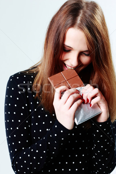 Young beautiful woman eating chocolate on gray background Stock photo © deandrobot