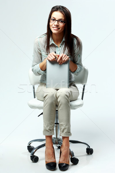 Young happy businesswoman sitting on office chair and holding tablet computer on gray background Stock photo © deandrobot