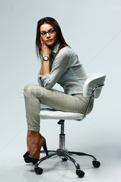 Young pensive woman sitting on the office chair on gray background Stock photo © deandrobot