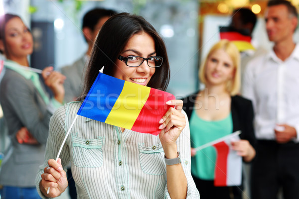 Happy businesswoman holding flag of Romania in front of colleagues Stock fotó © deandrobot