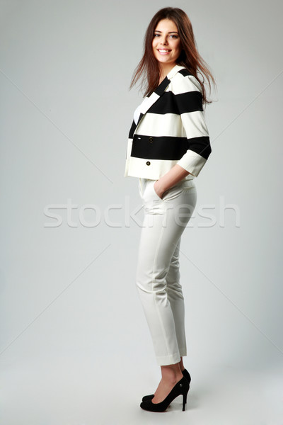 Full-length portrait of a young smiling woman in casual clothes on gray background Stock photo © deandrobot