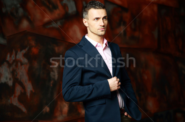 Fashionable pensive man standing over industrial background Stock photo © deandrobot