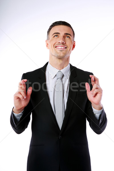 Businessman making a wish and looking up over gray background Stock photo © deandrobot
