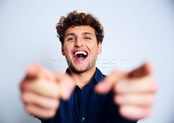 Portrait of a laughing man pointing at you Stock photo © deandrobot