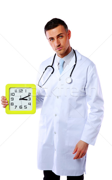 Confident male doctor holding clock isolated on white background Stock photo © deandrobot