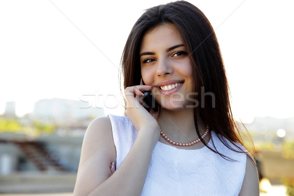 Portrait of a smiling woman speaking on the phone outdoors Stock photo © deandrobot