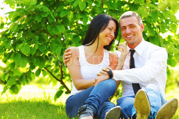 Portrait of beautiful young couple sitting on the grass in the park in sunny weather Stock photo © deandrobot