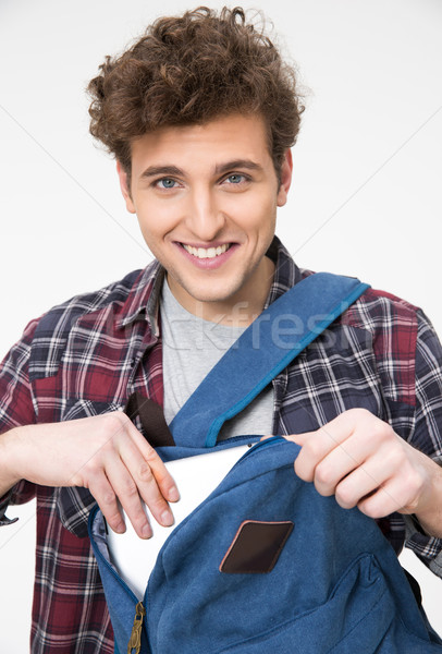 Happy male student pulls out of a backpack something  Stock photo © deandrobot