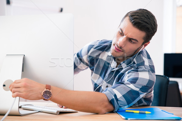 Businessman in casual cloth connecting cord to PC  Stock photo © deandrobot