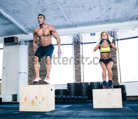 Stock photo: Group of man and woman jumping on fit box