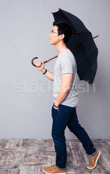 Stock photo: Man walking with umbrella
