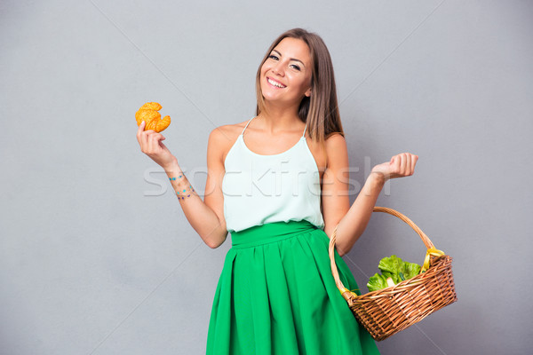 Woman holding basket with vegetables and bagel  Stock photo © deandrobot