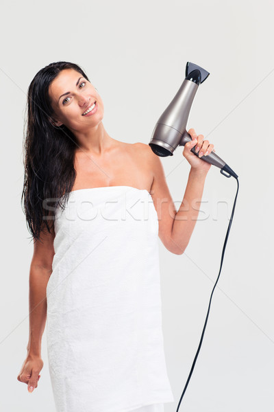 Happy woman in towel holding hairdryer  Stock photo © deandrobot