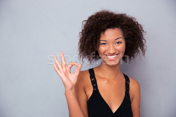 Smiling black woman showing ok sign  Stock photo © deandrobot