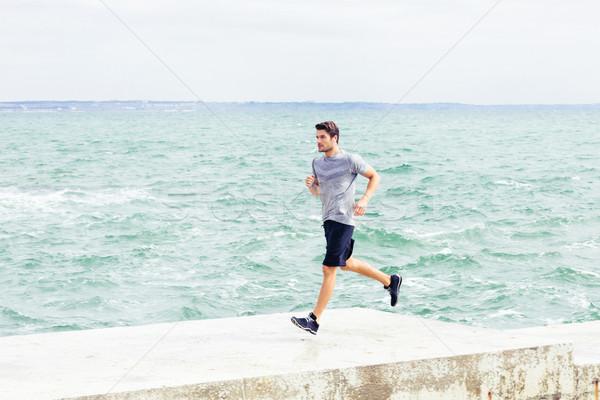 Homem corrida pier praia retrato moço Foto stock © deandrobot