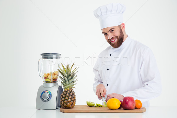 Stock photo: Portrait of a smiling male chef cook cutting fruits