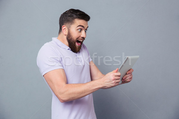 Cheerful casual man using tablet computer Stock photo © deandrobot