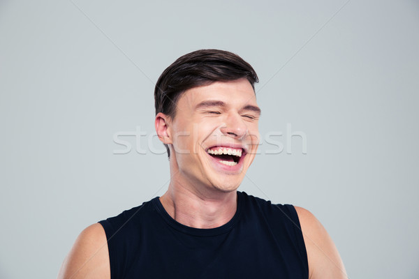 Portrait of a laughing man standing Stock photo © deandrobot