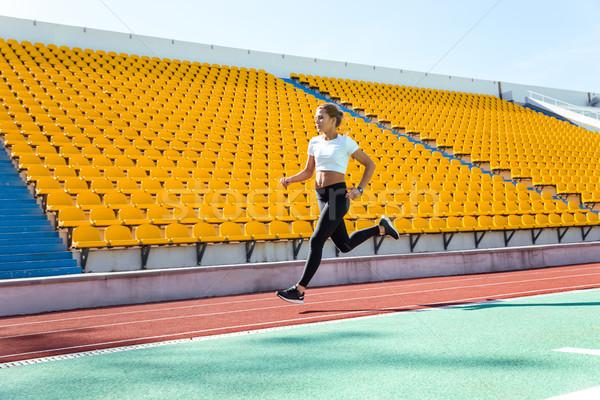 Woman running on stadium Stock photo © deandrobot