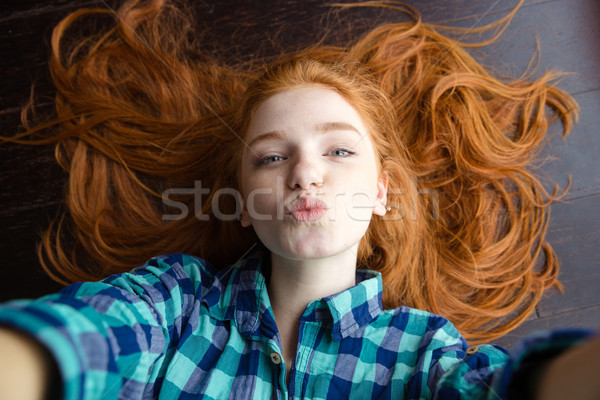 Top view of woman making selfie and sending air kiss  Stock photo © deandrobot