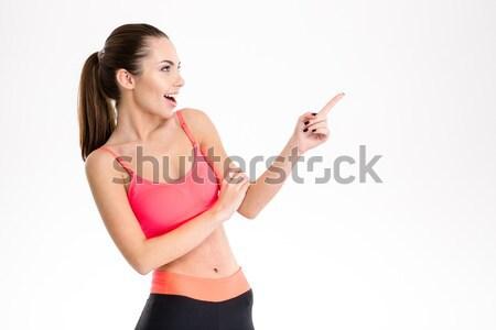Pozitív boldog fiatal sportoló mutat messze Stock fotó © deandrobot