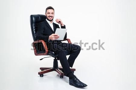 Thoughtful attractive businessmansitting in office chair and using mobile phone Stock photo © deandrobot