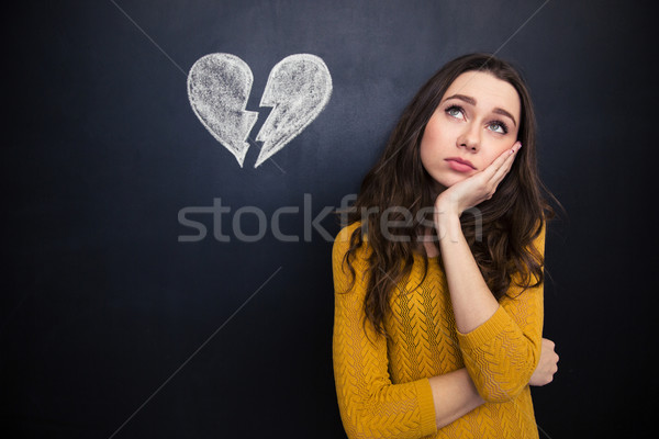 Upset woman thinking over chalkboard background with drawn broken heart Stock photo © deandrobot