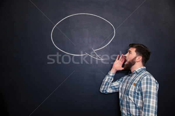 Handsome man shouting against chalkboard background with drawn speech bubble Stock photo © deandrobot