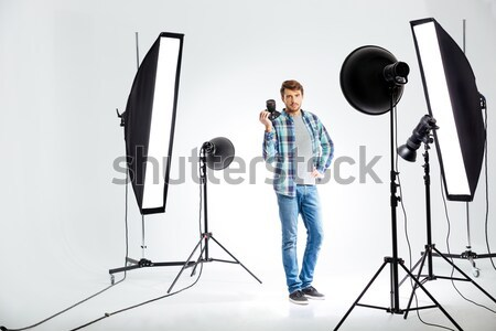 Photographer standing in studio with equipments Stock photo © deandrobot