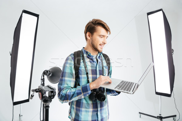 Photographer using laptop computer in studio Stock photo © deandrobot