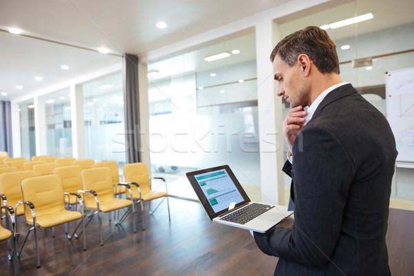Peinzend zakenman laptop permanente lege conferentie Stockfoto © deandrobot
