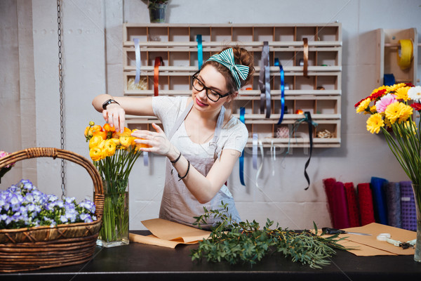 Smiling woman florist taking care of roses in flower shop Stock photo © deandrobot