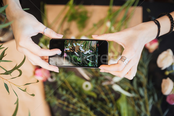 Florist holding smartphone and taking photos of flower on table Stock photo © deandrobot