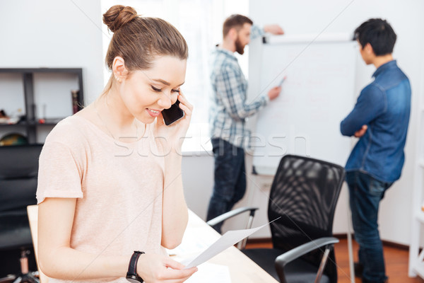 Stock photo: Cheerful businesswoman talking on mobile phone in office