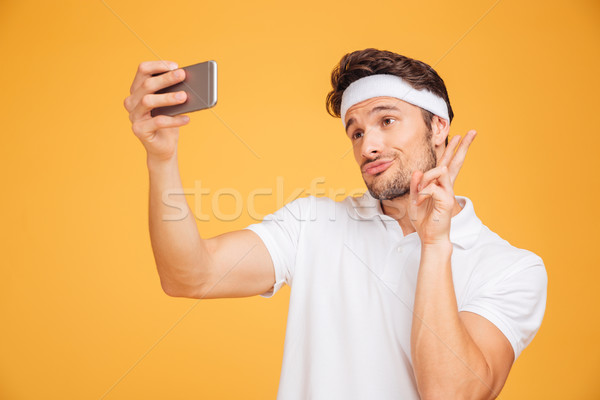 Smiling young sports man taking selfie and showing v sign Stock photo © deandrobot