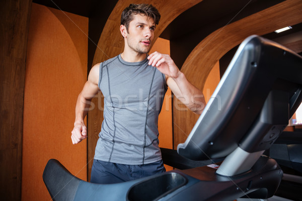Young man in sportswear running on treadmill at the gym Stock photo © deandrobot